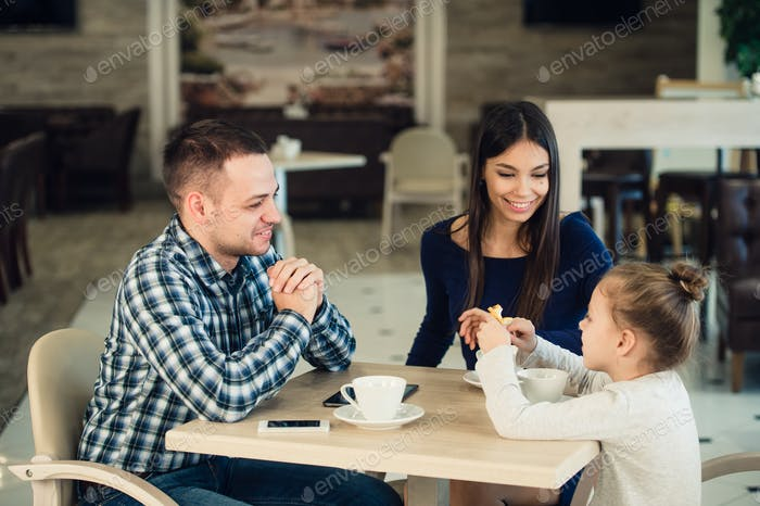 Family Enjoying tea In Cafe Together