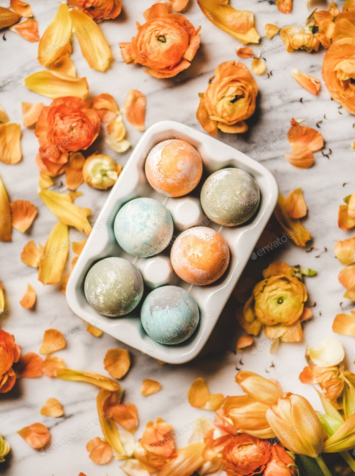 Colorful dyed Easter eggs over blooming orange flowers on marble