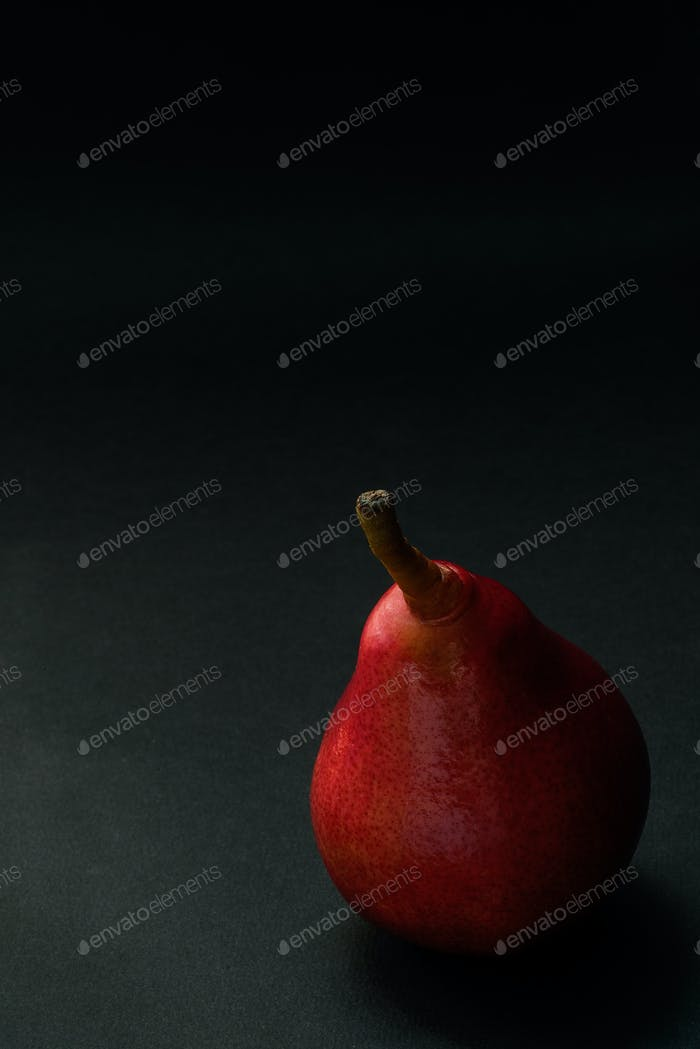 Red pear over dark background