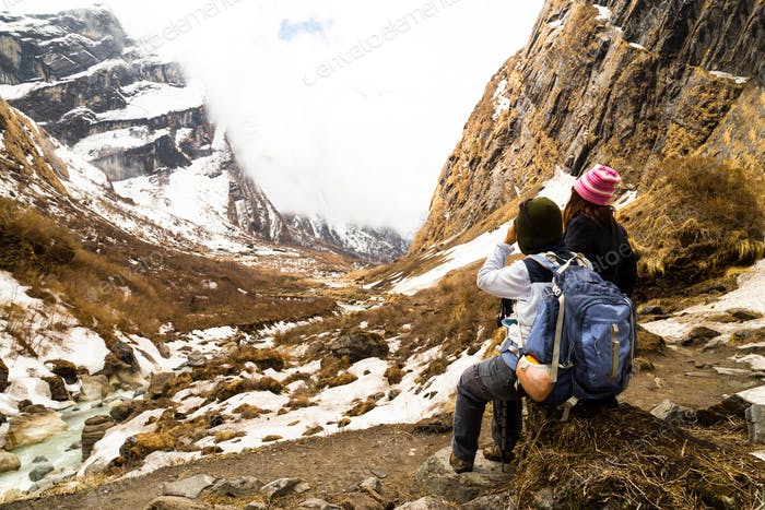 Two female hikers resting while enjoying the serene view of the snowy trek at Annapurna Nepal