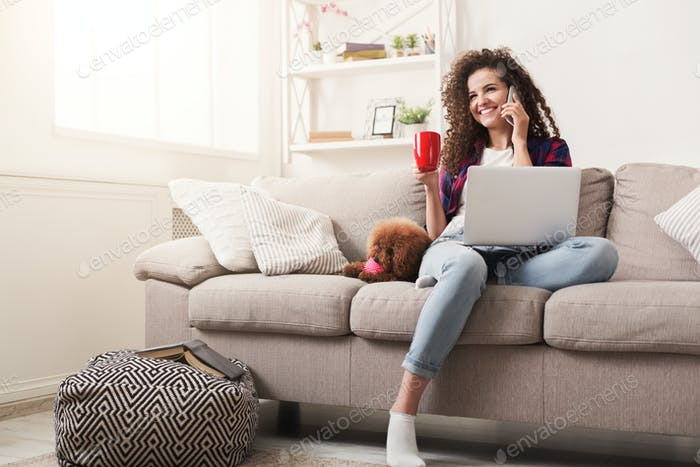 Smiling young woman with mobile, laptop and little dog at home