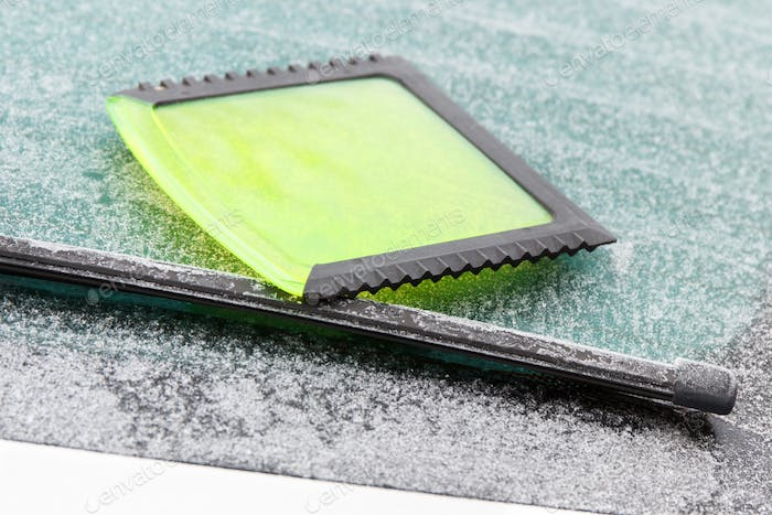 Green ice scraper on car windscreen, winter problems in transportation