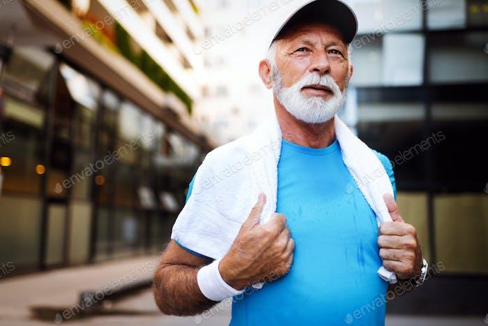 Porträt von athletischen reifen Mann nach Lauf. Schöner Senior Mann ruht nach Joggen im Park