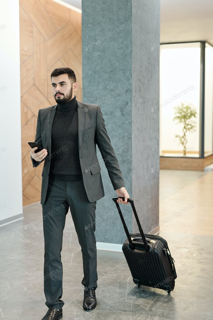 Young businessman with mobile phone pulling suitcase with baggage in hotel