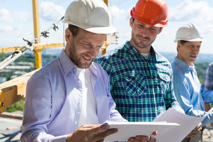 Architect And Builders Looking At Buiding Plan Blueprint Wearing Hardhat While Meeting On