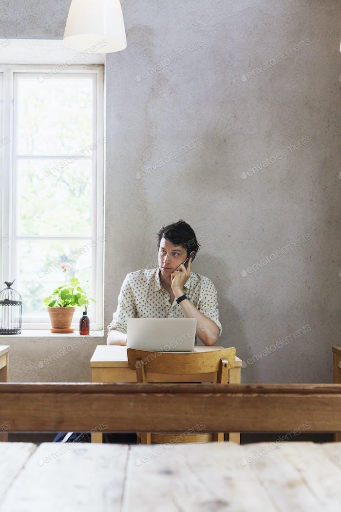 Geschäftsmann mit Handy während der Verwendung von Laptop im Restaurant