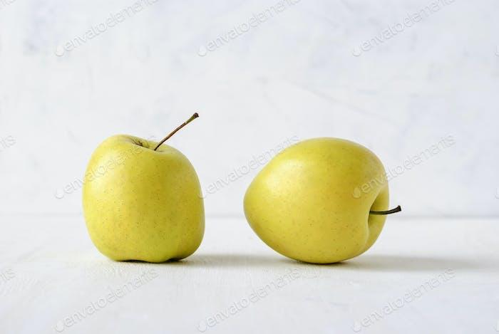 Two ugly misshapen golden fresh apples