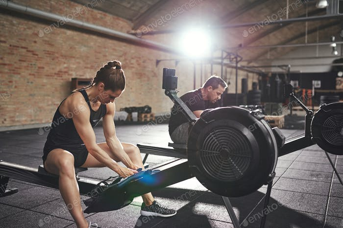 Man and woman training on rowing machines