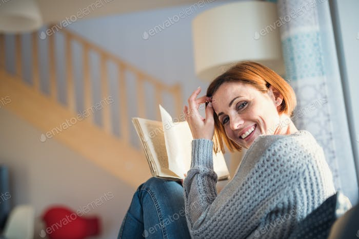 A young woman sitting indoors on a sofa at home, reading a book.