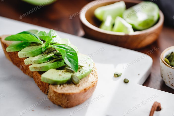 Avocado toast with pepitas and fresh basil on a white marble cutting board