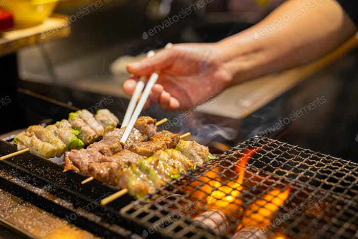 Vendor preparing meat on barbecue grill in Japan