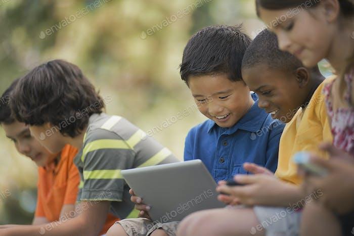 Eine Reihe von Kindern sitzen im Sommer im Freien mit Tablets und Handheld-Spielen.