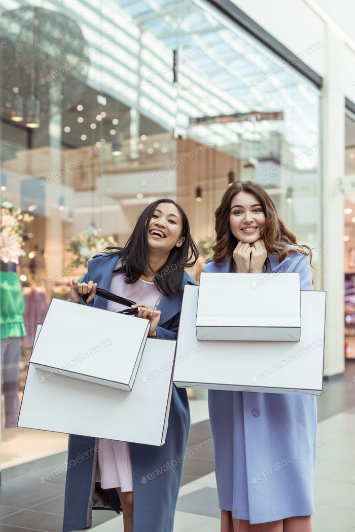 Happy attractive girls with shopping bags