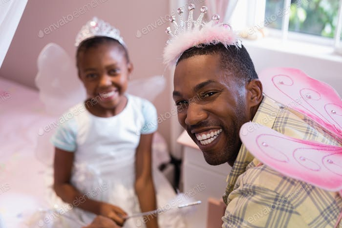 Cheerful father and daughter wearing costume wings at home