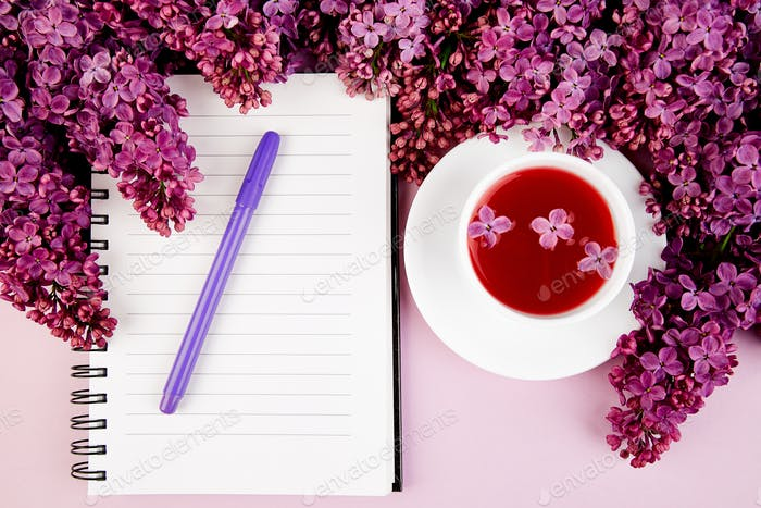 Cup of tea, diary and bouquet  lilac