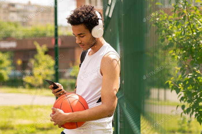 Young handsome athlete in sportswear listening to music in headphones