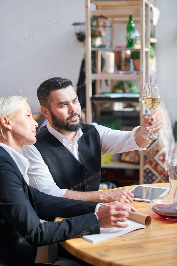 Two colleagues consulting about characteristics of one of wine samples
