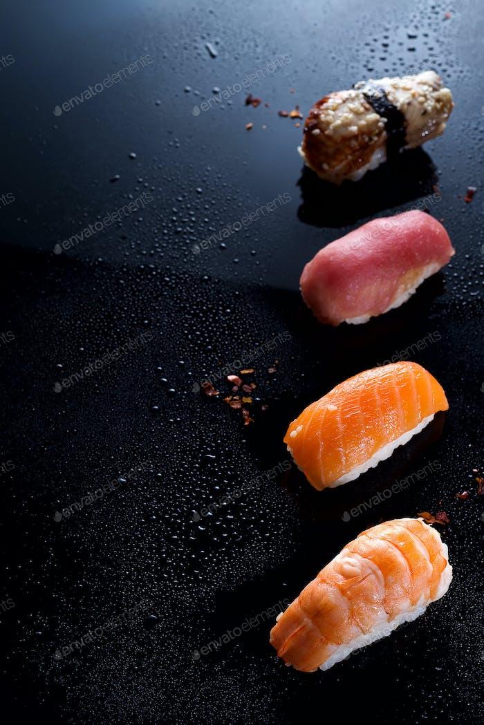 Sashimi, uramaki and nighiri, Japanese dish consisting of rice, salmon or tuna, shrimp in black with