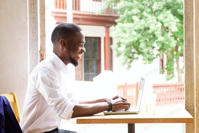 Handsome african businessman smiling with laptop