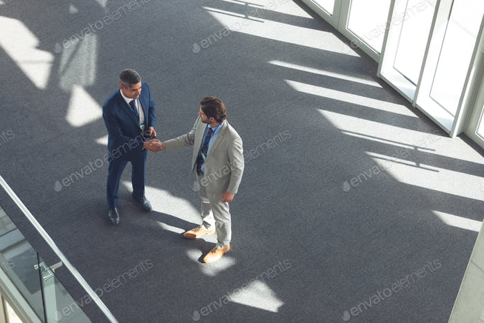 High angle view of Caucasians businessmen shaking hands in modern office building