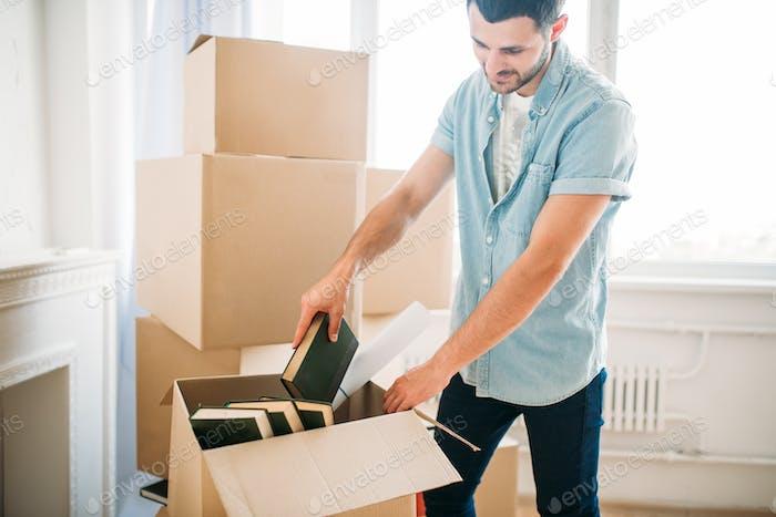 Young man unpacking cardboard boxes, housewarming