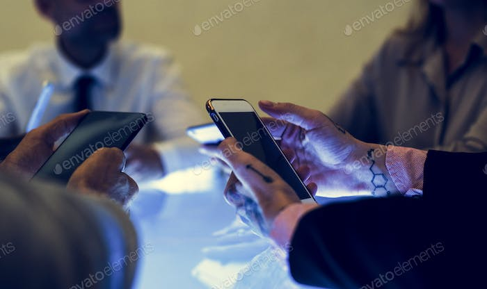 People holding smartphone in a meeting