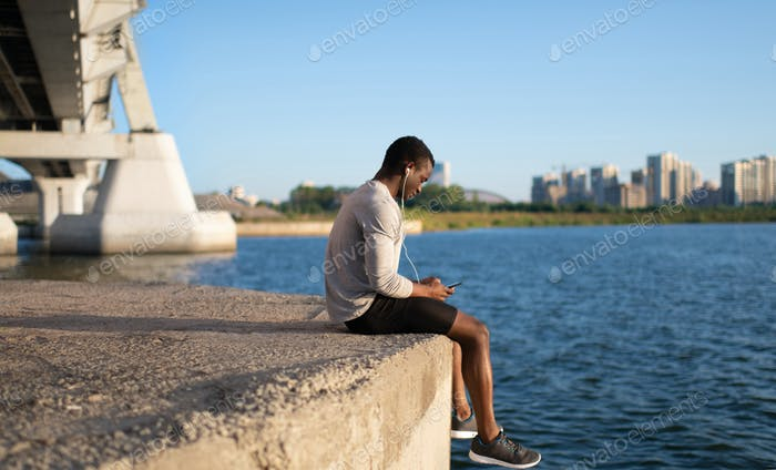 Young sportsman sitting with smartphone by river