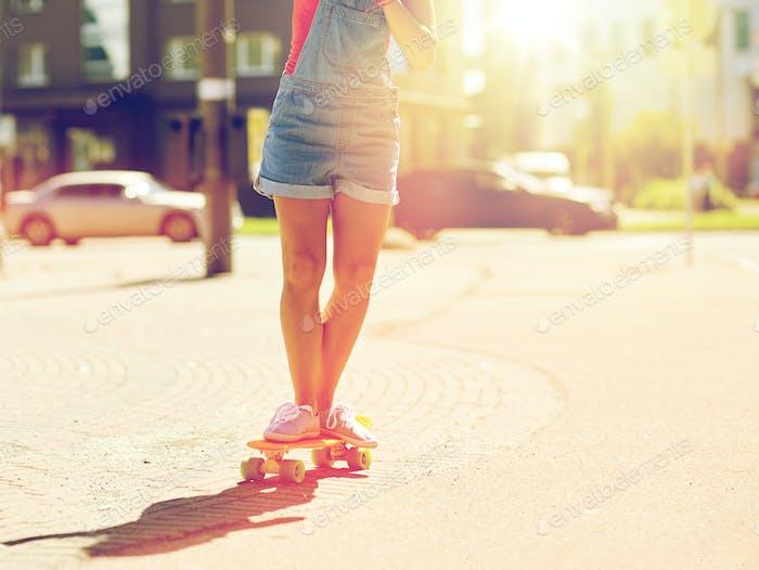 teenage girl riding skateboard on city street