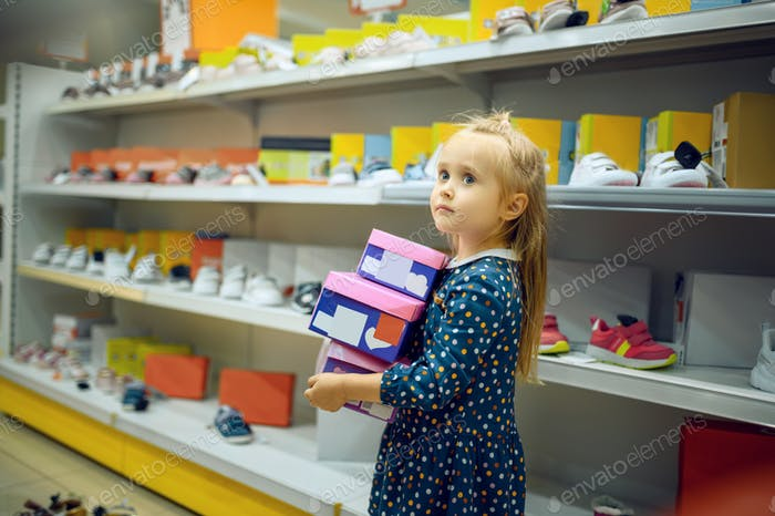 Little girl holds box with shoes in kid's store