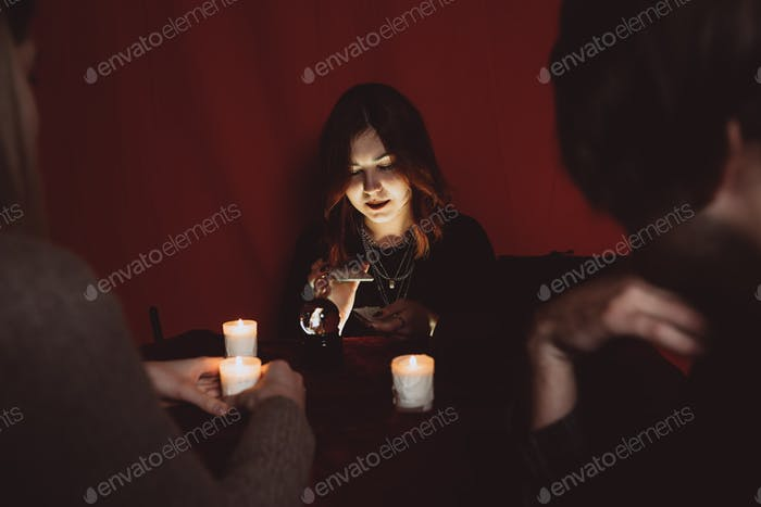 Group of people and woman fortune teller with crystal ball
