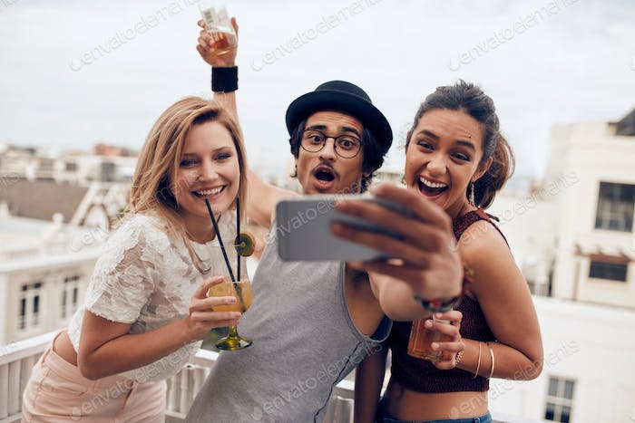 Excited young people taking self portrait in party