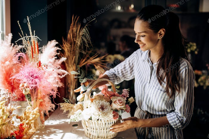 Florist collections a bouquet in the basket from fresh flowers of pastel colors in the flower shop