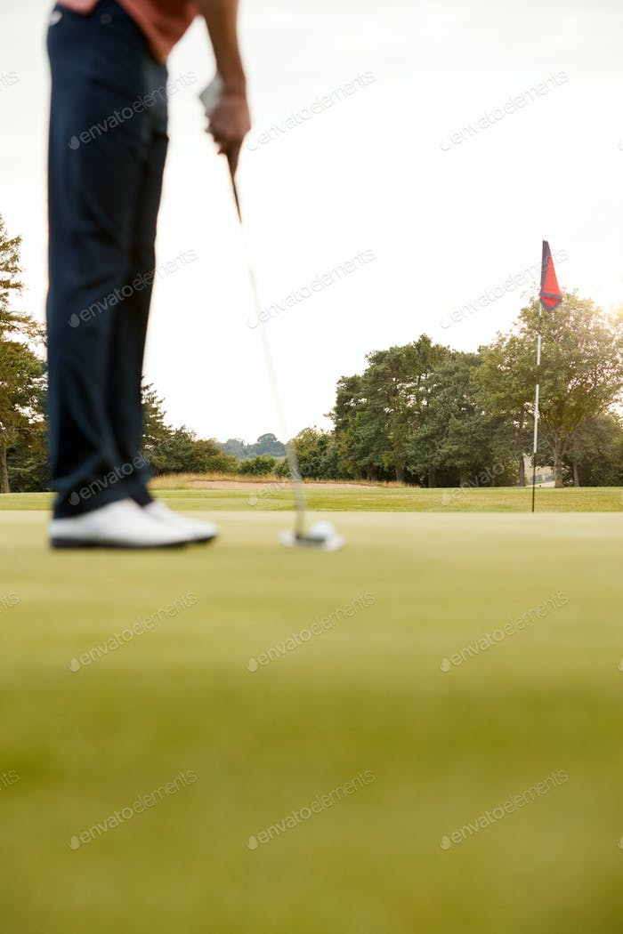 Close Up Of Female Golfer Putting Ball On Green