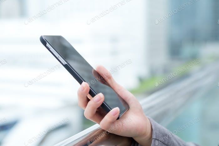 Businesswoman sending text message on smartphone