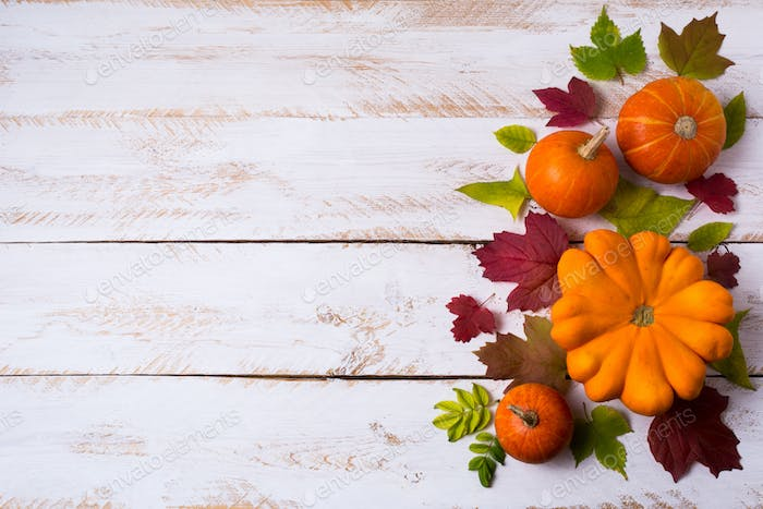 Rustic fall decor with pumpkins, red and green leaves