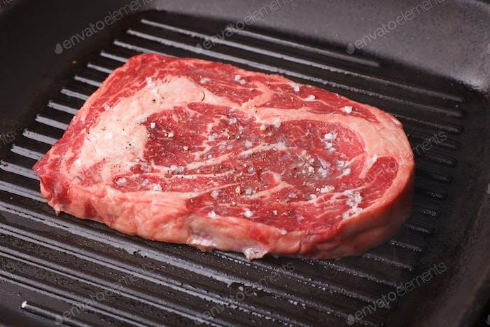raw ribeye on grill pan