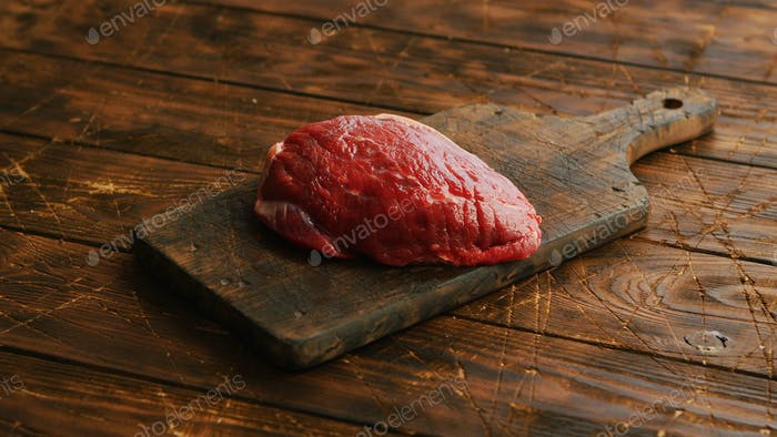Big fresh piece of meat laid on wooden cutting board