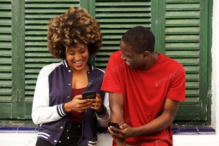 laughing couple standing together with mobile phone