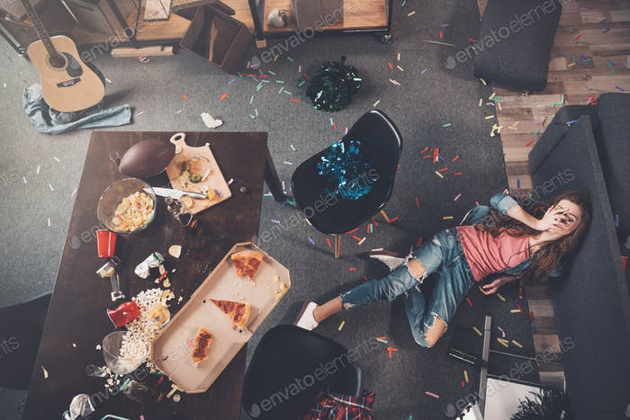 Top view of young drunk woman lying on floor in messy room