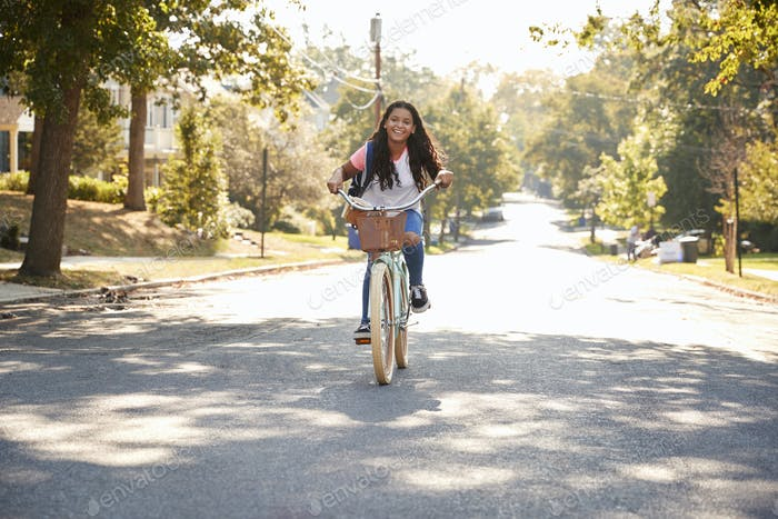 Girl Riding Bike Along Street To School
