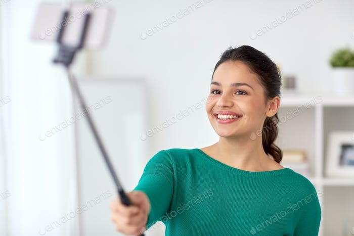 woman taking selfie by smartphone monopod at home