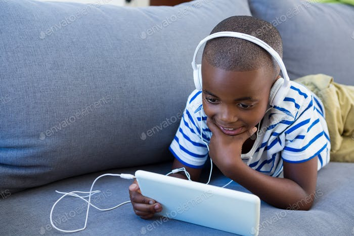Boy using digital tablet while listening to headphones on sofa at home