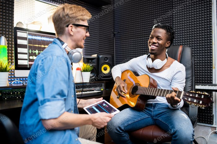 Happy African man with guitar and his colleague working over new soundtrack
