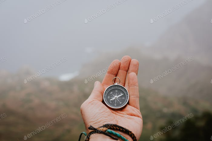 Looking at the compass to figure out right direction. Foggy valley and mountains in background