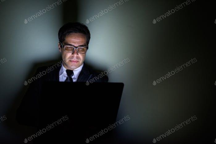 Handsome persischen Geschäftsmann mit Laptop in dunklen Raum