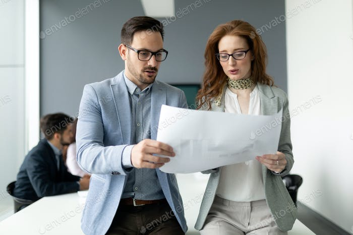 Confident business people reviewing project in office