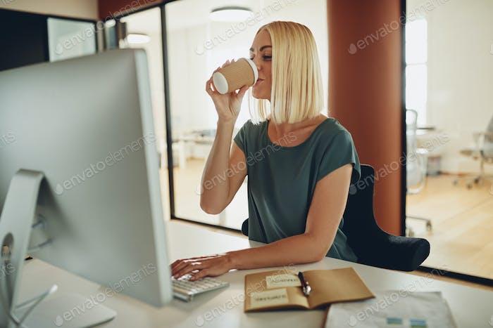 Junge Geschäftsfrau trinken einen Kaffee an ihrem Schreibtisch