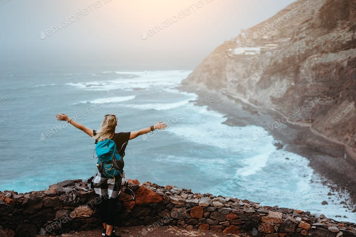 Tourist girl is happy to be on the end of long trekking route leading along cliff coastline with
