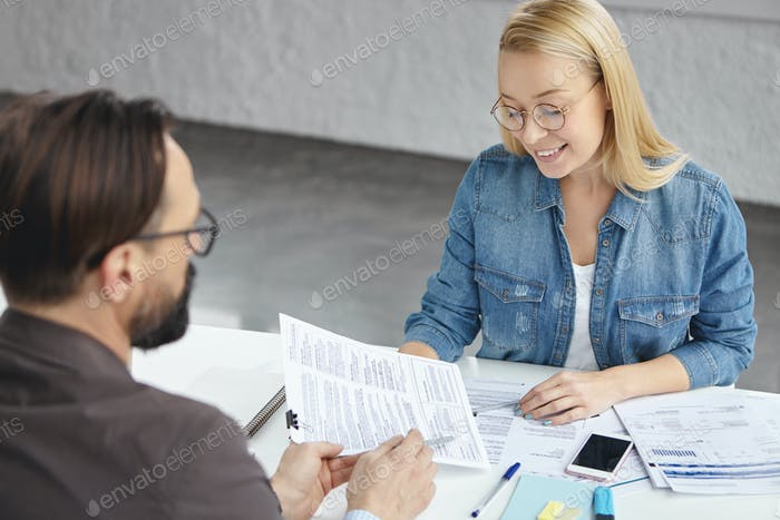 Two female and male partners analyze business data, deal with important case, work with business doc