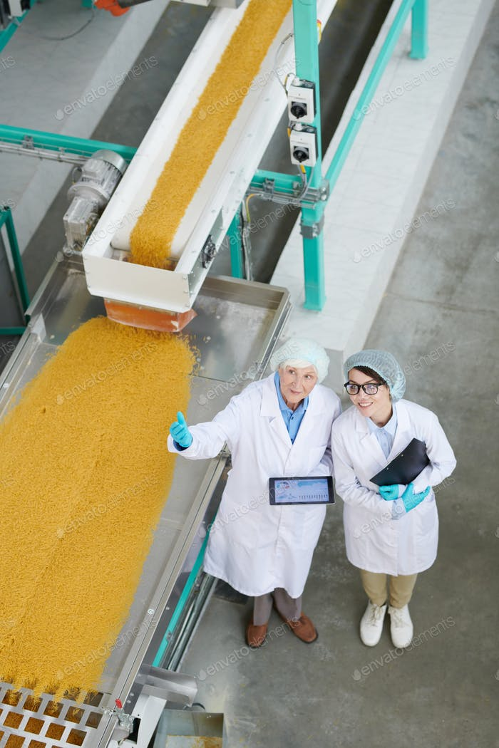 Two Workers Overseeing Production at Factory